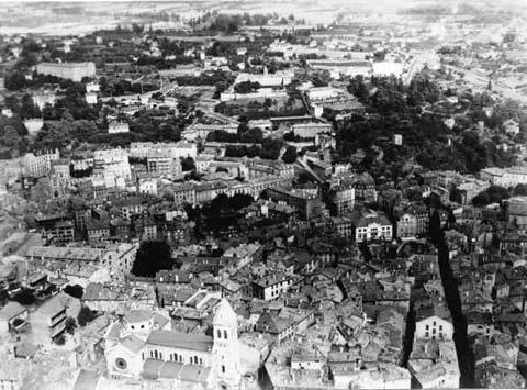 Vue aérienne Henrard v. 1950 (1) : Les quartiers de Notre-Dame, de la place de la Liberté et de celle des Cordeliers, au loin, le collège du Sacré-Cœur. Cliché / HENRARD, extrait des collections des Archives départementales de l'Ardèche